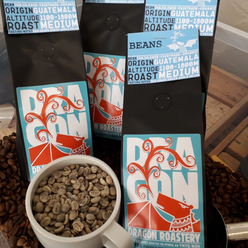 Dragon Roastery coffee beans packs with a cup full of green beans